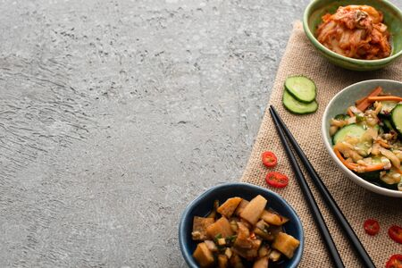 top view of bowls with tasty kimchi near chopsticks, sliced cucumber and chili pepper on sackcloth on concrete surface