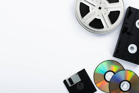 top view of CD discs, black VHS cassette, diskette and film reel on white background