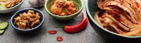 panoramic shot of kimchi in bowls, chili pepper and garlic on concrete surface