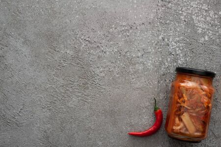 top view of red chili pepper and kimchi jar on grey concrete background 스톡 콘텐츠
