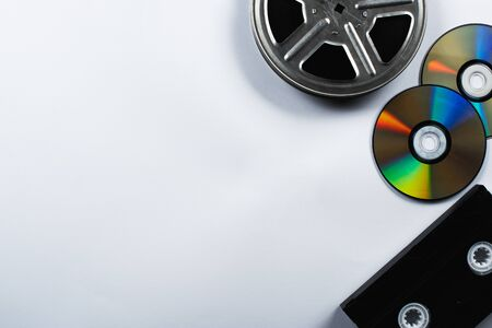 top view of CD discs, VHS cassette and film reel on white background Stock Photo