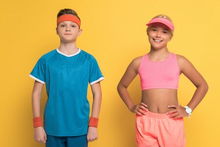smiling kids in sportswear looking at camera on yellow background