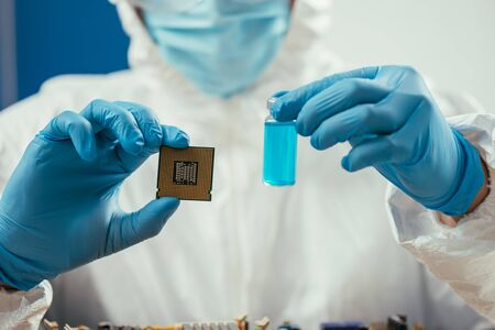 cropped of engineer holding computer microchip and glass container with blue liquid