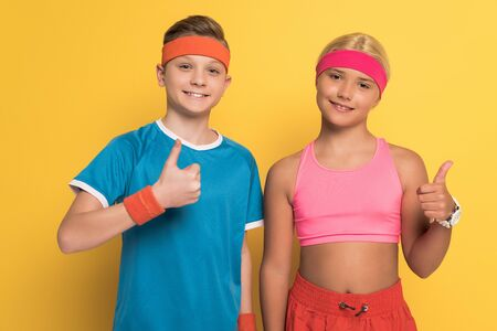 smiling kids in sportswear showing thumbs up on yellow background