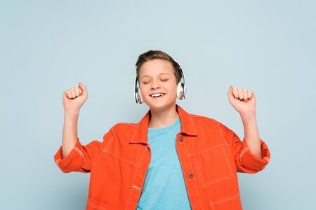 smiling boy with headphones listening to music on blue background Stockfoto
