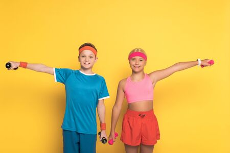 smiling kids in sportswear training with dumbbells on yellow background