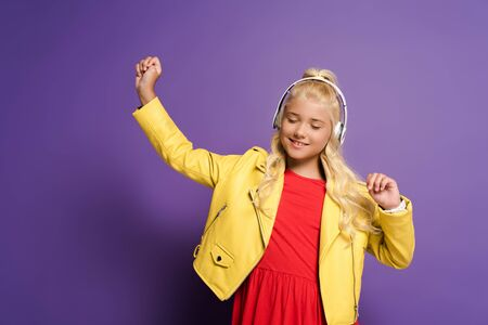 smiling kid with headphones listening to music and dancing on purple background