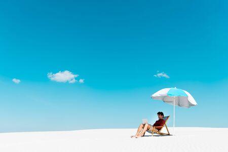 freelancer sitting with laptop in deck chair under umbrella on sandy beach against blue sky