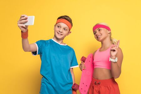 smiling boy taking selfie and his friend holding penny board and showing peace gesture on yellow background