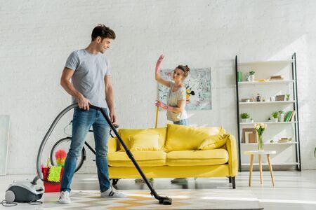 happy man using vacuum cleaner near woman waving hand in living room Stock Photo