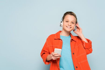 smiling kid with headphones listening to music and holding smartphone on blue background Stockfoto
