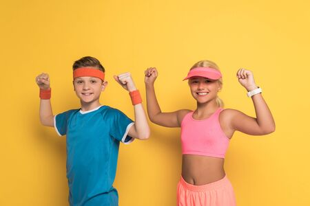 smiling kids in sportswear showing strong gesture on yellow background