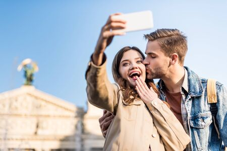 Selective focus of man kissing excited girlfriend taking selfie with smartphone