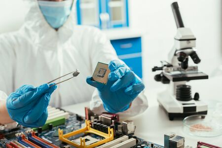 cropped view of engineer holding microchip and small stone near microscope and computer motherboard 版權商用圖片