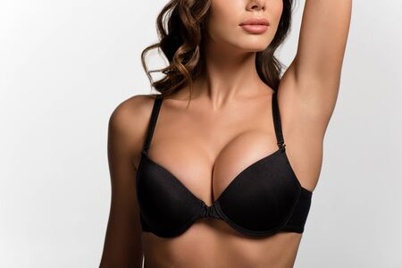 cropped view of sexy girl with big breasts posing with raised hand isolated on white Banco de Imagens