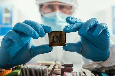 selective focus of engineer holding microchip near computer motherboard 版權商用圖片