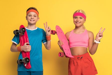 smiling kids in sportswear holding penny boards and showing peace gesture on yellow background