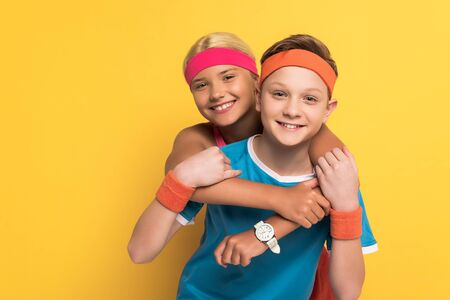 smiling kids in sportswear hugging and looking at camera on yellow background