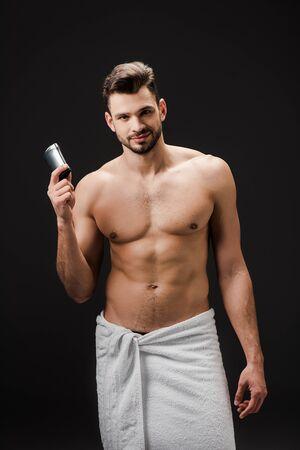 smiling man holding deodorant isolated on black