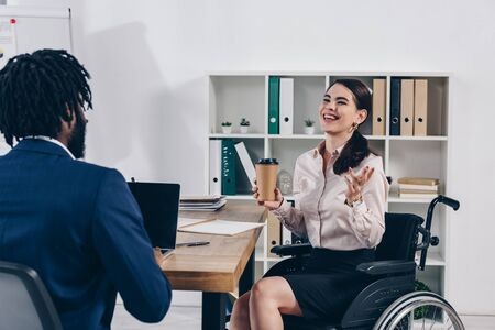 Disabled employee on wheelchair with paper cup of coffee laughing near african american recruiter with laptop Imagens