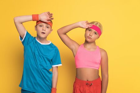 tired kids in sportswear touching heads on yellow background