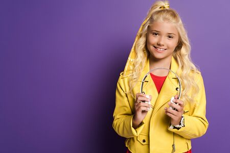smiling and cute kid holding headphones on purple background