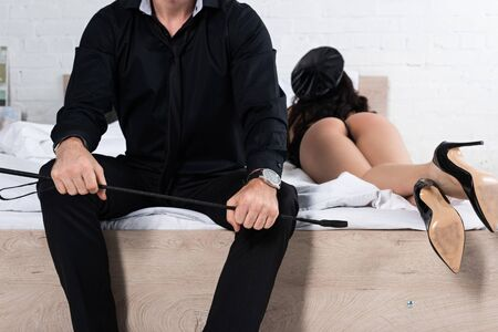 Selective focus of man with flogging whip and policewoman lying on bed