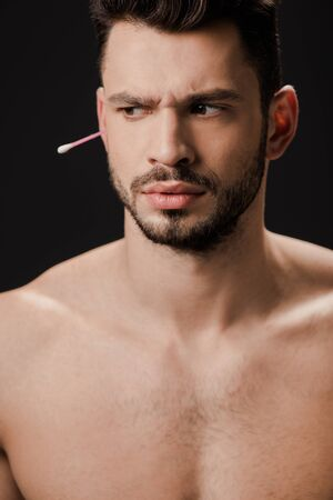 thoughtful naked man with ear swab isolated on black 版權商用圖片