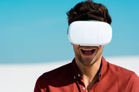 excited man on beach in vr headset against clear blue sky