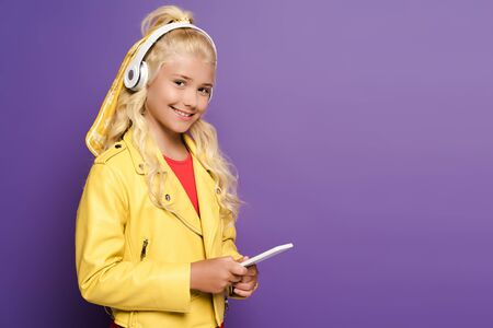 smiling kid with headphones holding smartphone on purple background