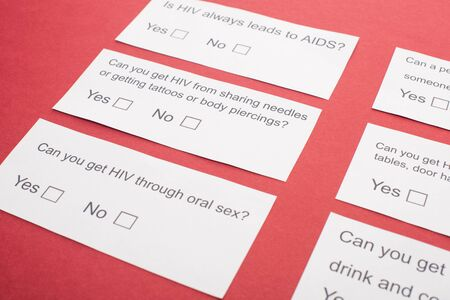 paper cards with HIV questionnaire on red background