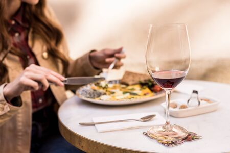 Partial view of woman eating with glass of wine in cafe