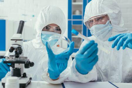 biochemists holding test tube and petri dish near microscope Stock Photo