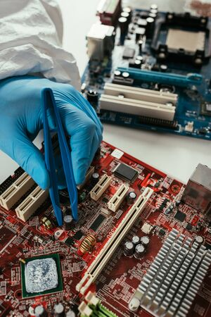 cropped view of engineer fixing computer motherboard with tweezers