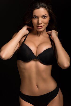 Chica sexy y coqueta con una gran sonrisa a la cámara mientras toca el cuello aislado en negro