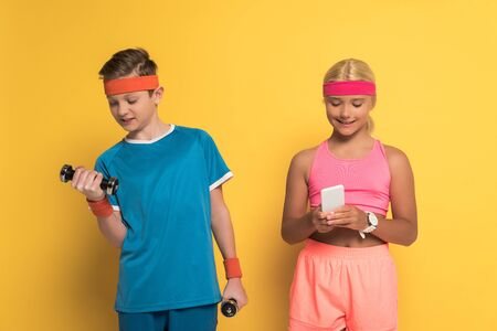 smiling boy training with dumbbells and his friend holding smartphone on yellow background Stock Photo