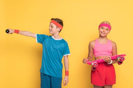 smiling boy training with dumbbell and his friend holding penny board on yellow background