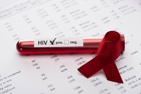 positive hiv blood sample test on paper result form with awareness ribbon