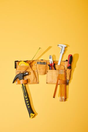top view of tool belt with hammer, measuring tape, pliers, calipers, screwdriver and folding ruler on yellow background Zdjęcie Seryjne