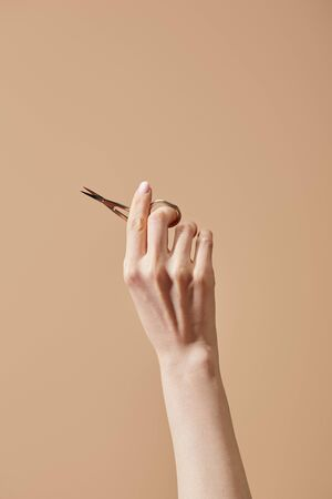 Cropped view of female hand with nail scissors isolated on beige