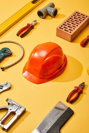 flat lay with industrial tools, helmet and brick, on yellow background 免版税图像