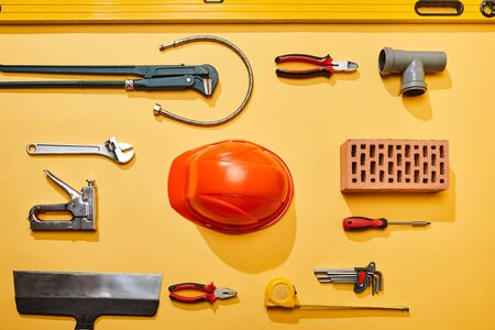 top view of industrial tools, helmet, plumbing hose and brick on yellow background