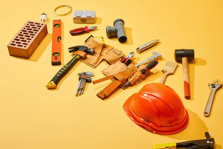 high angle view of tool belt with industrial tools, brick and helmet on yellow background Zdjęcie Seryjne