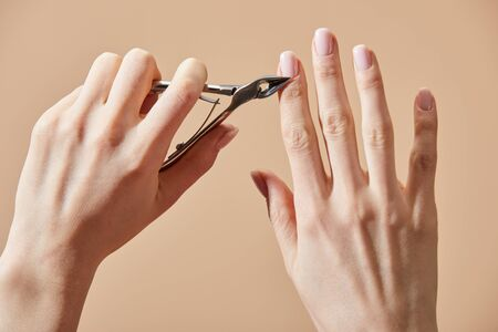 Cropped view of woman cutting cuticle using nipper isolated on beige