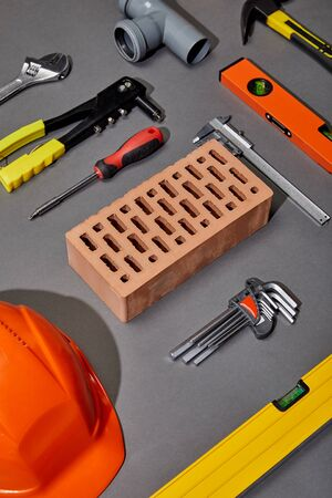 flat lay with orange helmet, brick, rivet gun, hammer, screwdriver, calipers, spirit level, angle keys and pipe connector on grey background Banque d'images