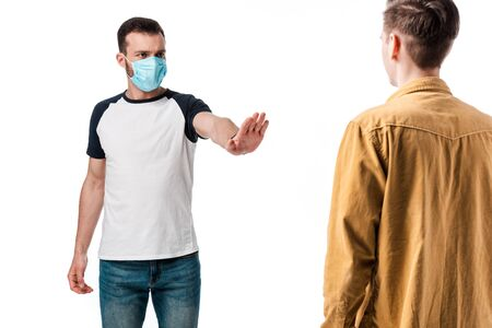 selective focus of man in medical mask showing stop gesture near guy isolated on white