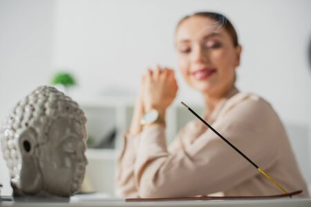 selective focus of happy businesswoman sitting in office with Buddha head and incense stick