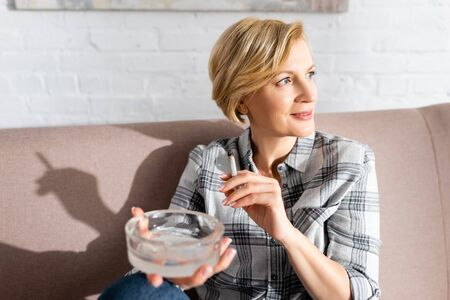 selective focus of happy and mature woman holding joint and ashtray Stock Photo