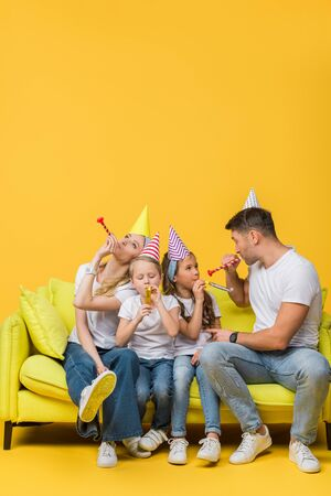 happy parents and children in birthday party caps with blowers on sofa on yellow