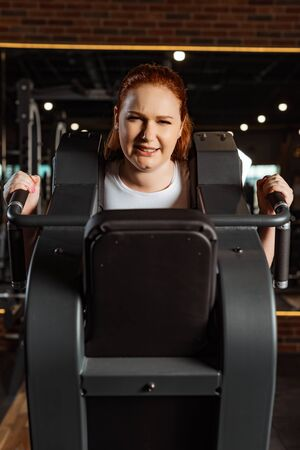purposeful overweight girl doing arms extension exercise on fitness machine